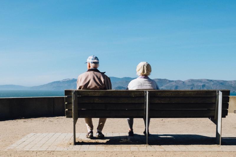 Deux personnes âgées en bonne santé assises sur un banc.